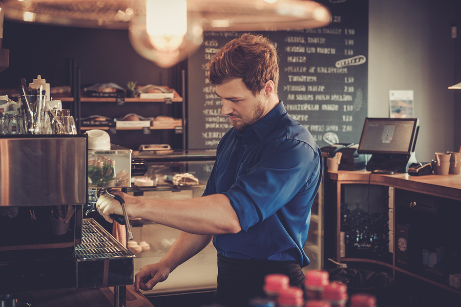 Handsome barista preparing cup of coffee for customer in coffee