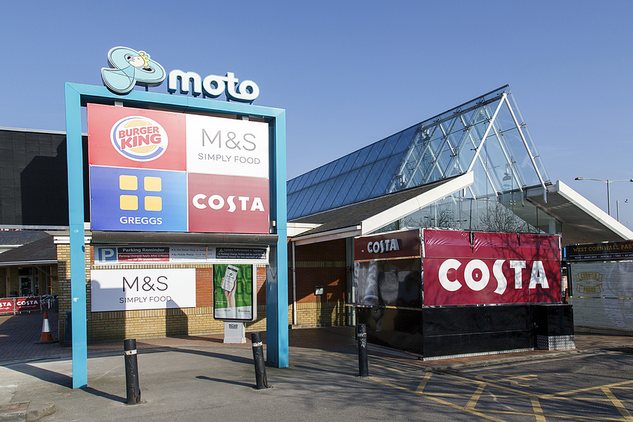 Motorway Services is a three burger rated service area on the M4 operated by Moto. With a blue sky background.
