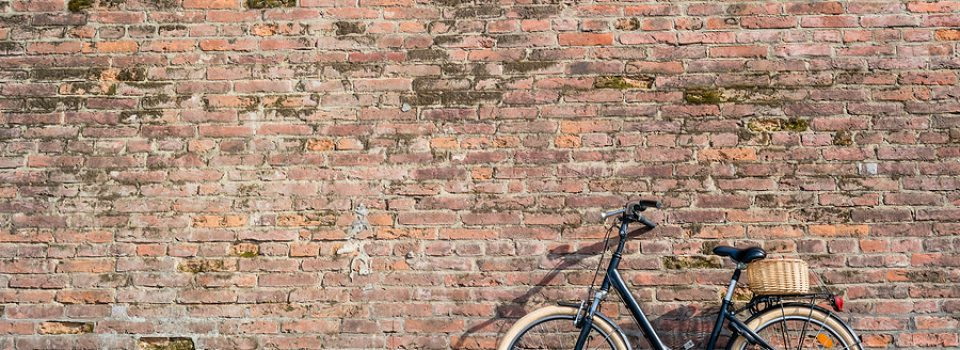 Black retro vintage bicycle with old brick wall and copy space. Retro bicycle with basket in front of the old brick wall. Retro bicycle on roadside with vintage brick wall background.