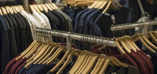 Wear hanging on rack in clothing store. Sale and shopping concept