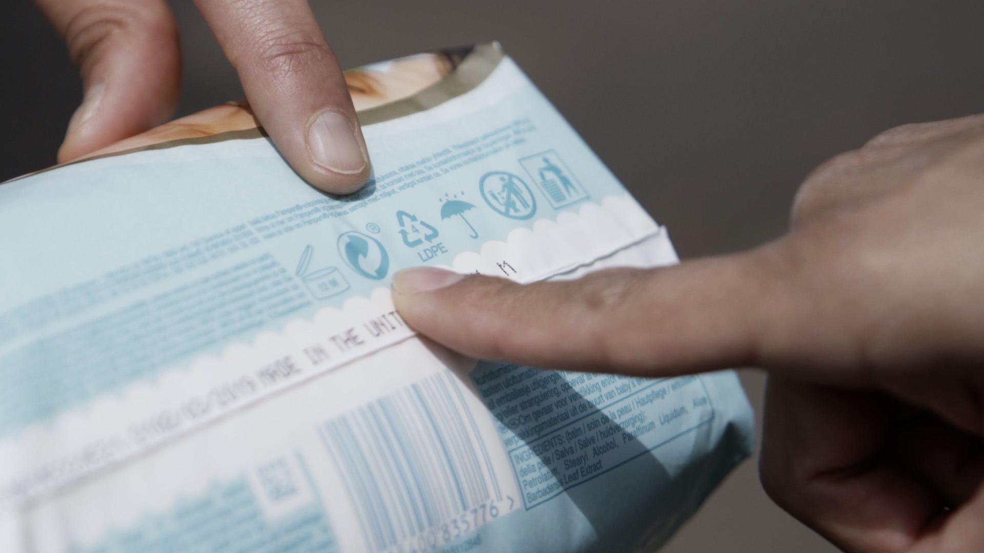 A person checking nappy packaging.