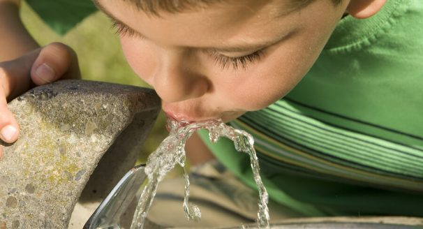 A picture of a little boy drinking from a water fountain.