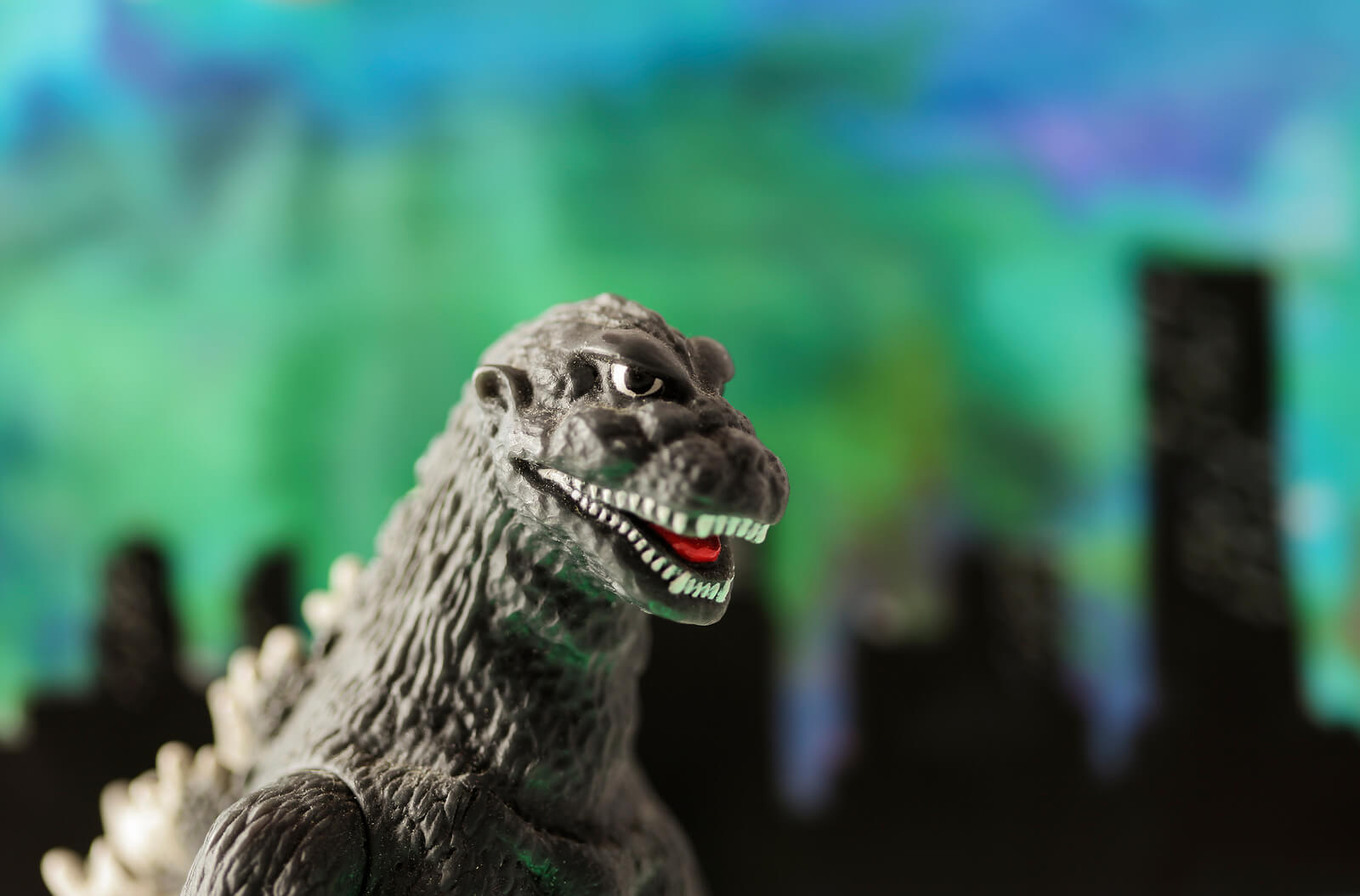 A Godzilla toy stands before a backround depicting a city.