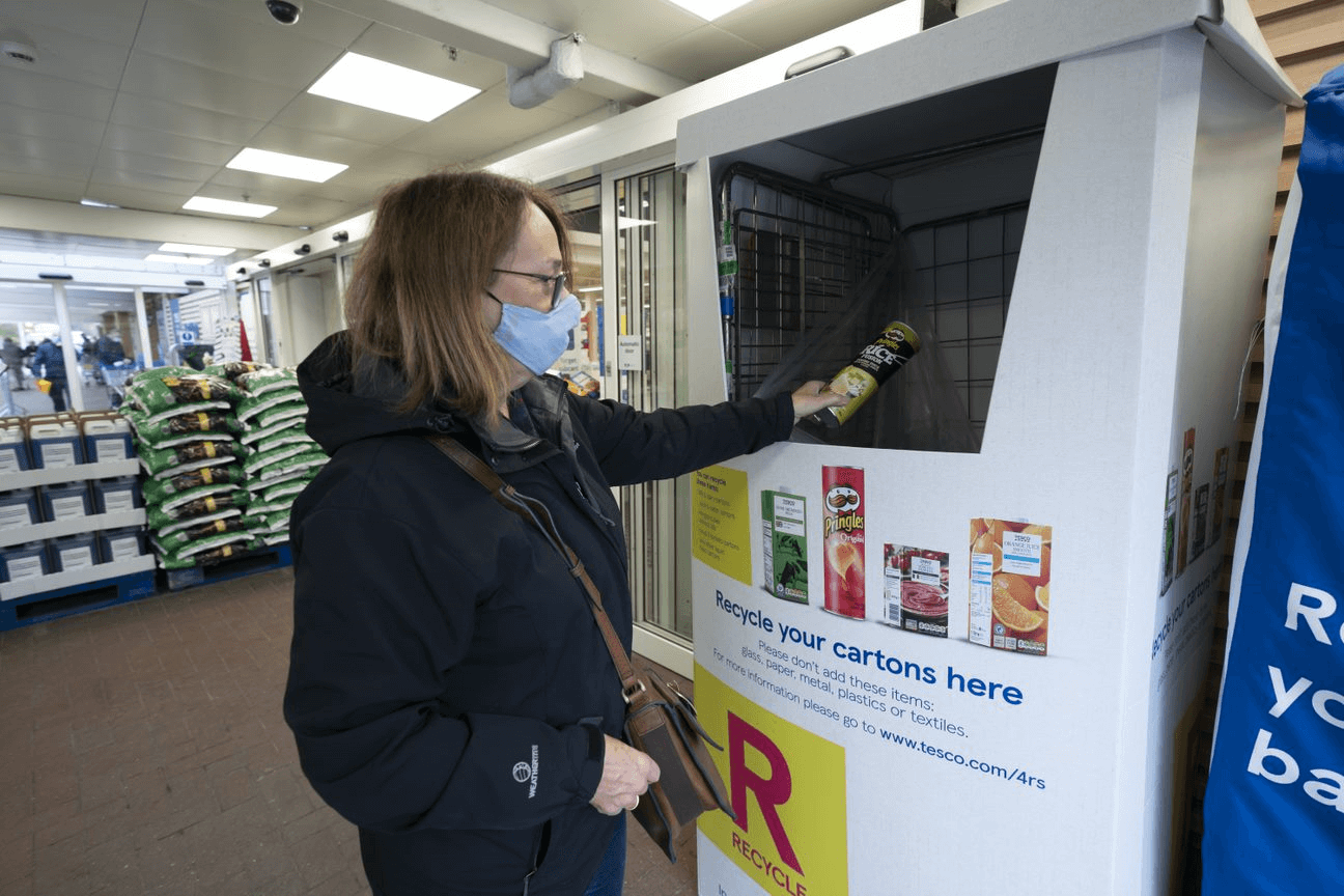 Tesco recycling point, with a woman dropping some plastic into it,