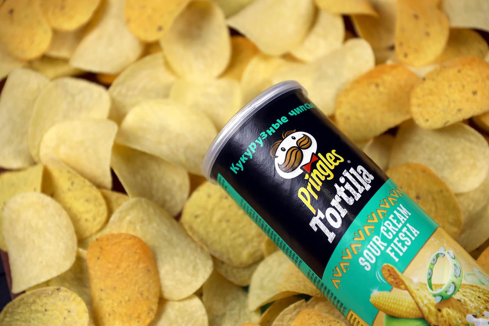 A tube of tortilla pringles lays across a golden bed of crisps.