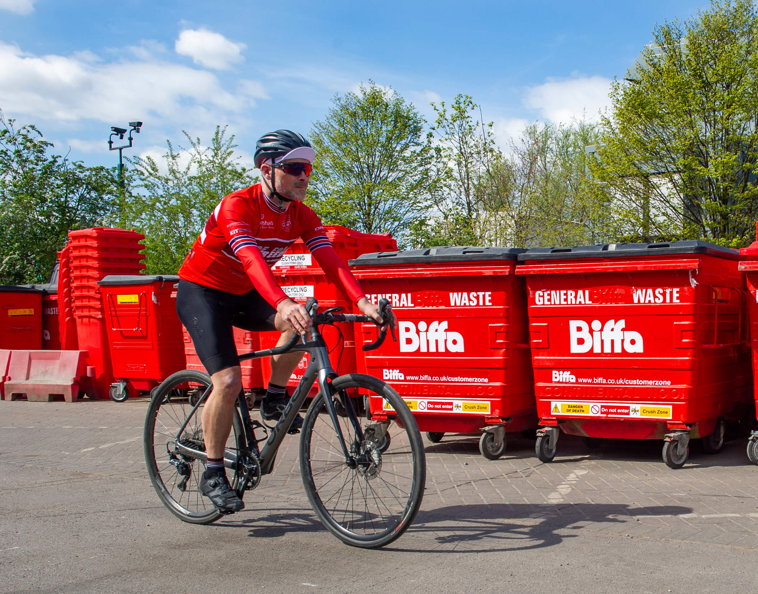 A cyclist on the Ride for Freedom rides past a row of large Biffa bins.